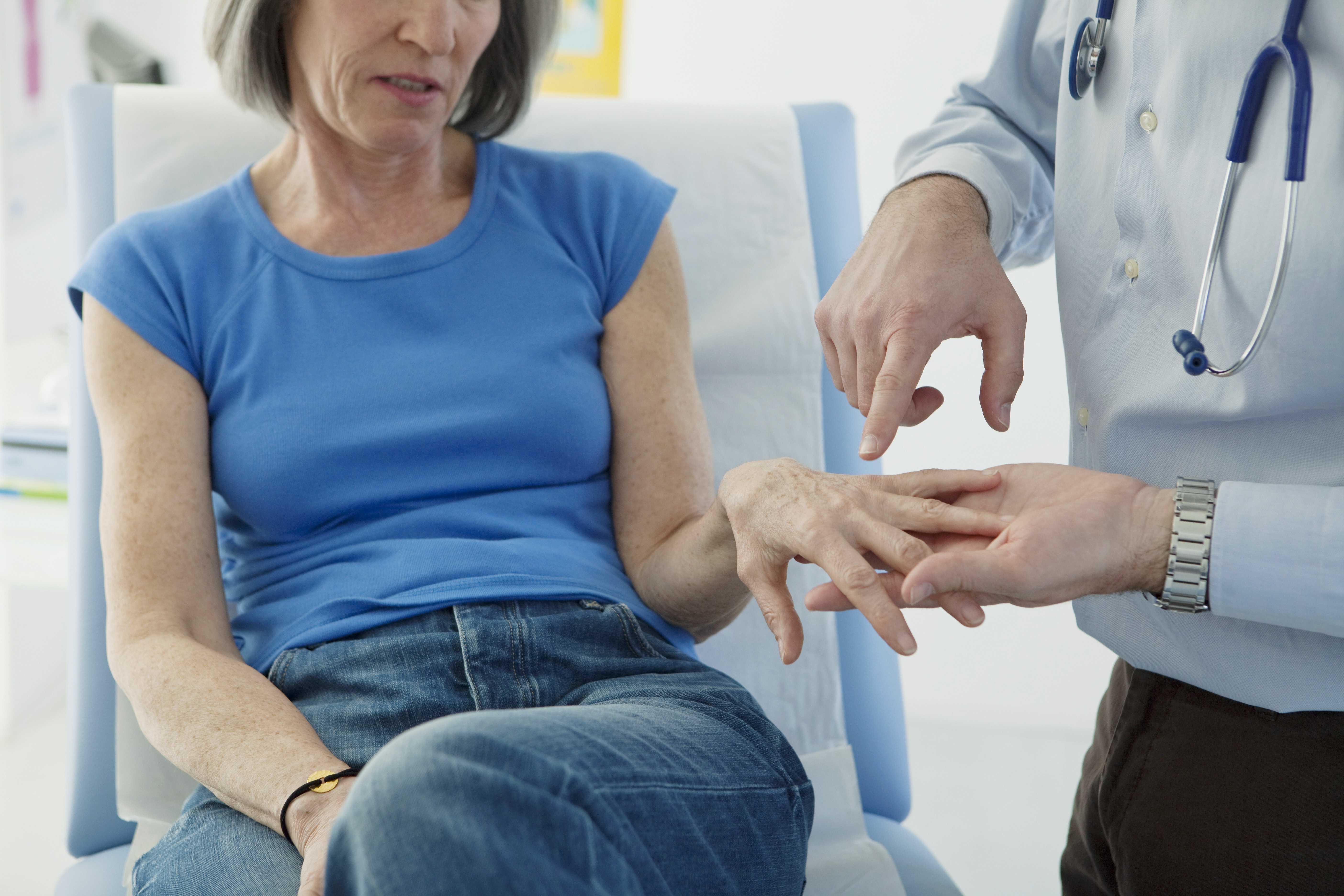 Doctor looking at patient with pain in hand