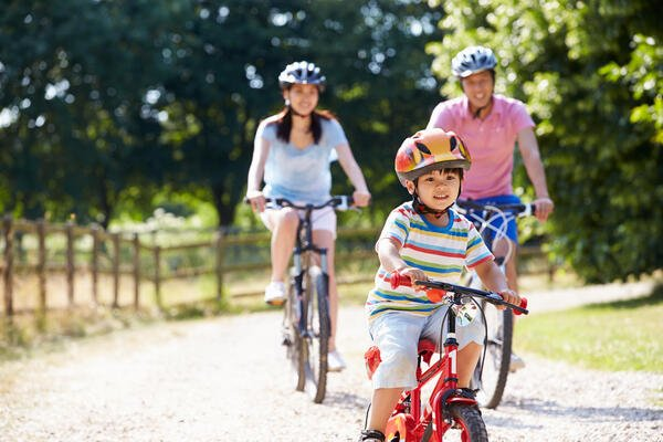 Family riding bikes together summer
