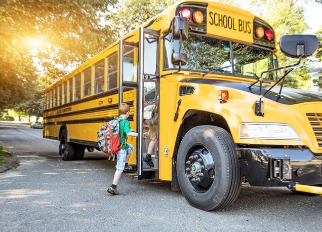 Young boy getting on school bus