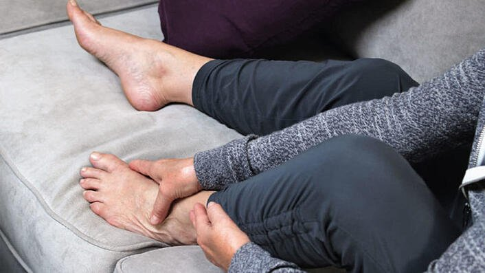woman holding foot in pain