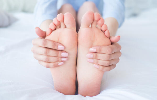 woman-holding-feet-sitting-on-bed-1
